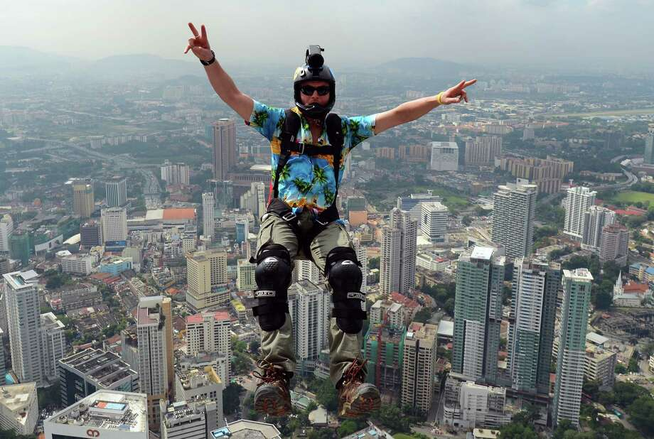Base jumper Scott Hiscoe from Australia leaps from the top of the 421-metre Kuala Lumpur Tower during the International Tower Jump in Kuala Lumpur on Sept. 27, 2012.  Some 95 professional basejumpers from 18 countries are taking part in the annual event.      AFP PHOTO / MOHD RASFAN Photo: AFP, Getty / 2012 AFP