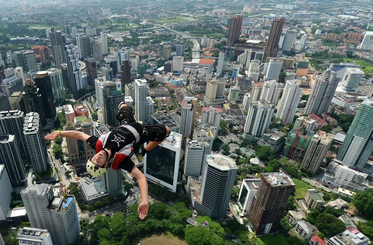 Base jumper Andrei Nefedov from Russia leaps from the top of the 421-meter Kuala Lumpur Tower during the International Tower Jump in Kuala Lumpur on Sept.r 27, 2012. Some 95 professional basejumpers from 18 countries are taking part in the annual event. AFP PHOTO / MOHD RASFAN