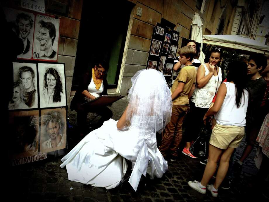 A bride poses for a portrait by a street artist in the center of Rome on Sept. 26, 2012.  AFP PHOTO/ Filippo MONTEFORTE Photo: FILIPPO MONTEFORTE, Getty / 2012 AFP