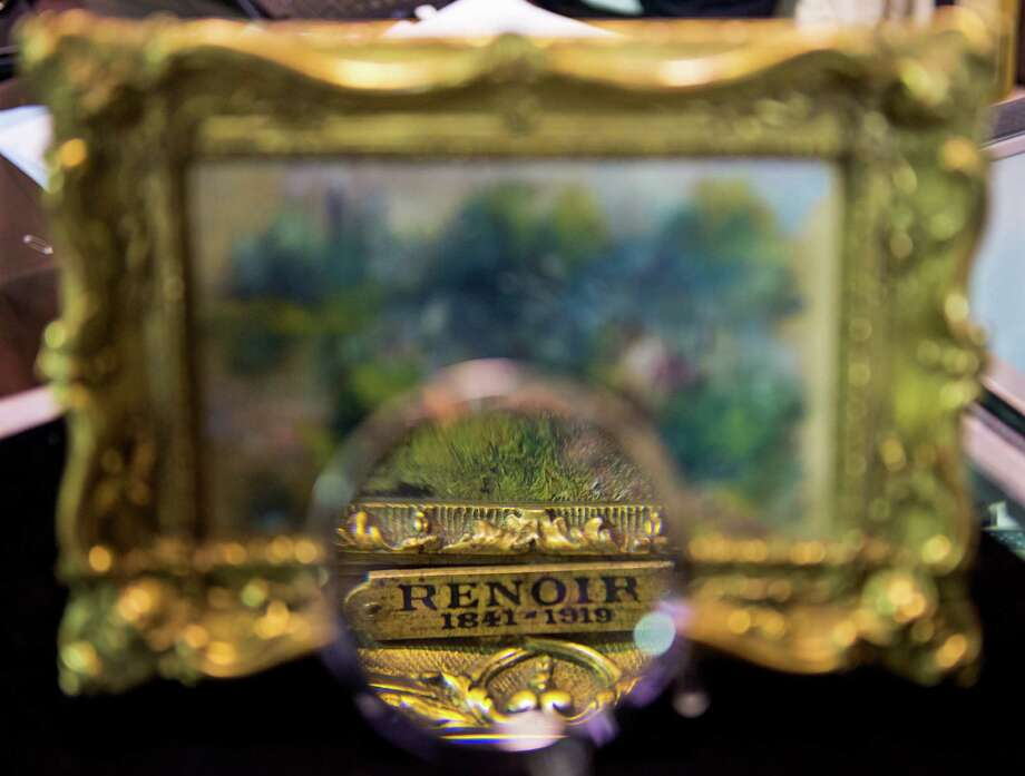 "An art shopper looks closely at a 5.5 inch by 6.6 inch painting by French Impressionist master Pierre-Auguste Renoir Sept. 25, 2012, in Alexandria, Va. The painting was recently discovered for just a few dollars at a Virgina flea market sale. The canvas which shows a scene along the Seine River titled ""Paysage Bords de Seine"" is scheduled to be auctioned Sept. 29, 2012a, selling for an expected $75,000 to $100,000. It was for sale in a box with a plastic cow and a Paul Bunyan doll  for $50and still carries a label from the Berheim-Jeune arthouse in Paris, a famous purveyor of works by Renoir.   AFP PHOTO/Paul J. Richards Photo: PAUL J. RICHARDS, Getty / 2012 AFP"