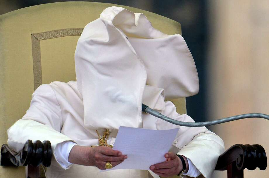 A gust of wind blows Pope Benedict XVI's collar into his face on Sept. 26, 2102, during his weekly general audience in Saint-Peter's square at the Vatican.     AFP PHOTO / VINCENZO PINTO Photo: VINCENZO PINTO, Getty / 2012 AFP