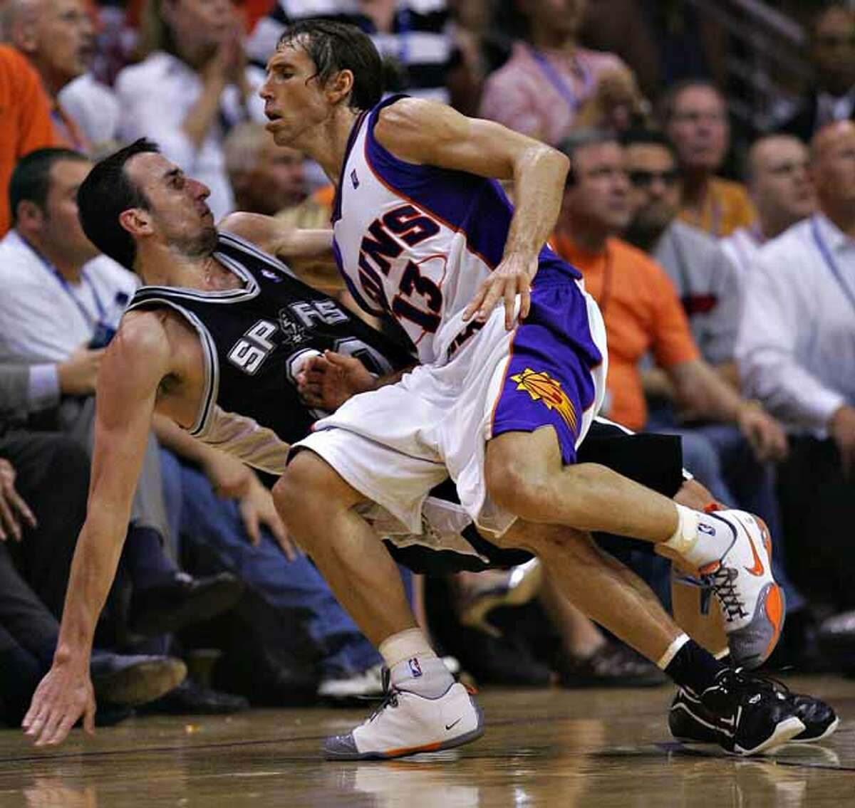 Spurs guard Manu Ginobili is fouled by Steve Nash on a three-point attempt in the second half of Game 5 of the Western Conference Semifinals on May 14, 2007, at the U.S. Airways Center.