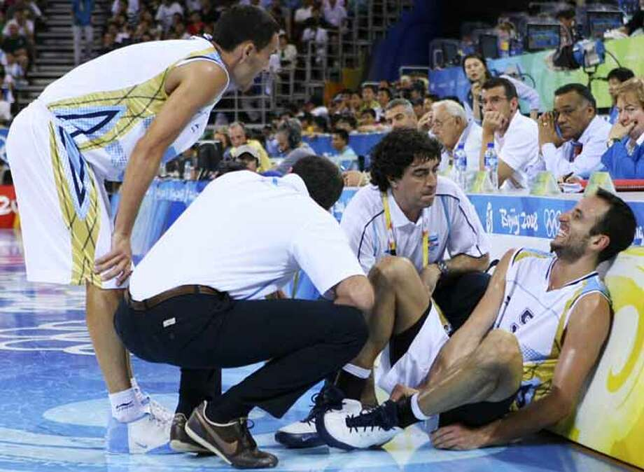 Argentina's Manu Ginobili (right) reacts after injuring his ankle during the first half of a semifinal game against Team USA at the 2008 Beijing Olympics on Aug. 22, 2008 in Beijing, China. The USA won 101-81. Photo: EDWARD A. ORNELAS, SAN ANTONIO EXPRESS-NEWS / eornelas@express-news.net