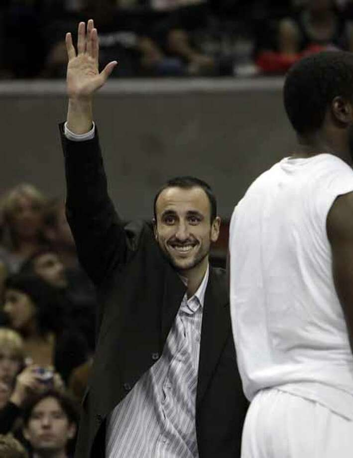 The Spurs' Manu Ginobili waves to the crowd during a break in action against the Washington Wizards at the AT&T Center on Nov. 21, 2009. Ginobili was sidelined with a strained left groin. Photo: Kin Man Hui, San Antonio Express-News / kmhui@express-news.net