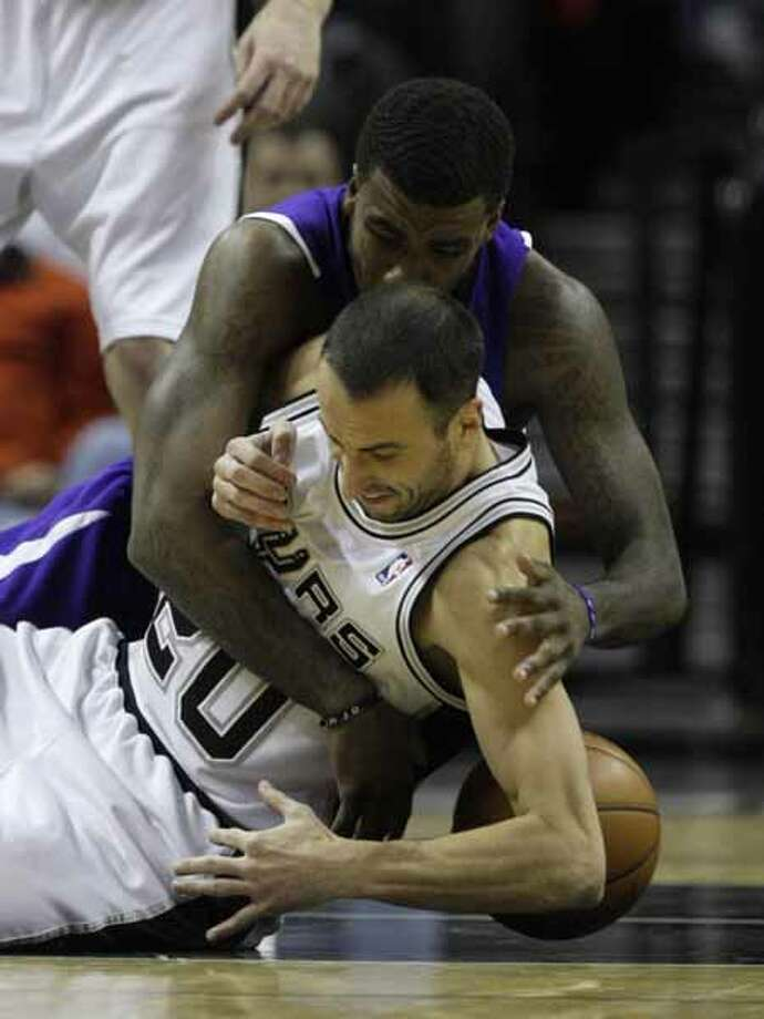 The Spurs' Manu Ginobili is fouled by the Sacramento Kings' Donte Greene during a scramble for the ball at the AT&T Center on Dec. 9, 2009. The Spurs won 118-106. Photo: JERRY LARA, San Antonio Express-News / glara@express-news.net