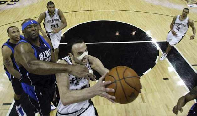 The Spurs' Manu Ginobili drives to the basket around the Dallas Mavericks' Erick Dampier during first half action of Game 6 of the first round of the NBA playoffs on April 29, 2010, at the AT&T Center. Photo: EDWARD A. ORNELAS, SAN ANTONIO EXPRESS-NEWS / © 2010 SAN ANTONIO EXPRESS-NEWS