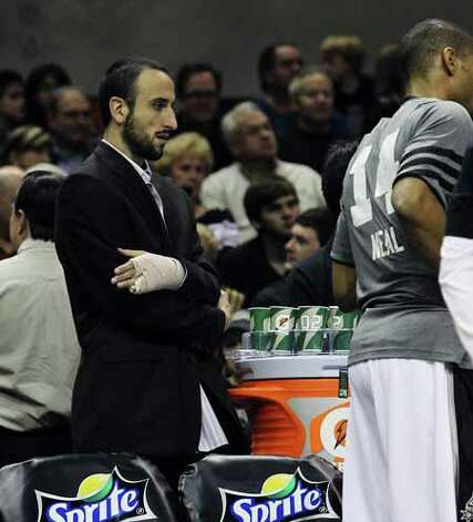 The Spurs' Manu Ginobili (left) is seen with his bandaged left hand on the sidelines during a game against the Golden State Warriors at the AT&T Center on Jan. 4, 2012. Photo: KIN MAN HUI, SAN ANTONIO EXPRESS-NEWS / SAN ANTONIO EXPRESS-NEWS
