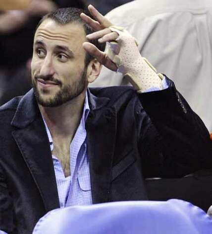 The Spurs' Manu Ginobili waves to fans from the bench during the first half against the Phoenix Suns on Jan. 15, 2012, at the AT&T Center. Photo: EDWARD A. ORNELAS, SAN ANTONIO EXPRESS-NEWS / SAN ANTONIO EXPRESS-NEWS (NFS)