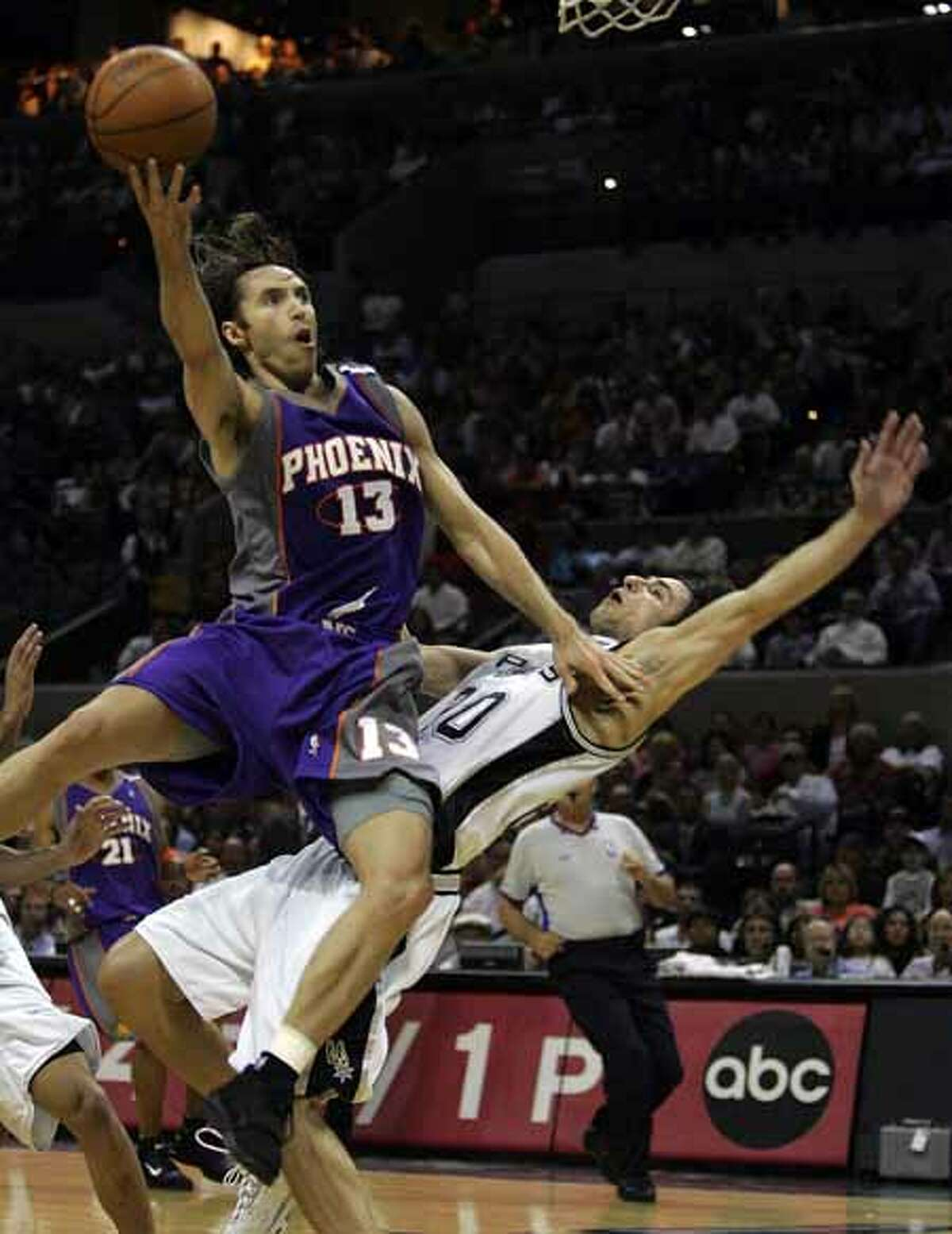 The Phoenix Suns' Steve Nash drives through the defense of the Spurs' Manu Ginobili during the first quarter of Game 4 of the Western Conference Finals at the SBC Center on May 30, 2005.