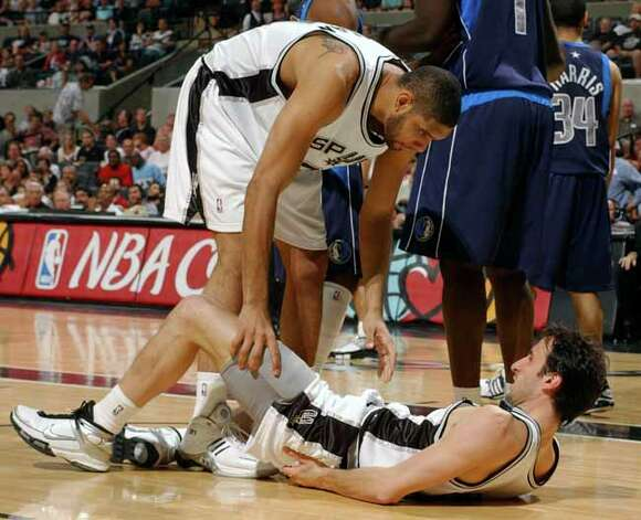 The Spurs' Tim Duncan checks on teammate Manu Ginobili after Ginobili was hit in the lip during the second game of the Spurs' Western Conference semifinals series against the Dallas Mavericks on May 9, 2006 at the AT&T Center. Photo: EDWARD A. ORNELAS, SAN ANTONIO EXPRESS-NEWS / SAN ANTONIO EXPRESS-NEWS