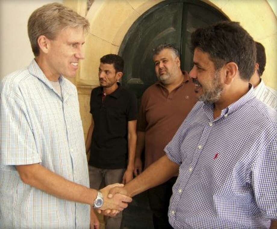 In this photo posted on the U.S. Embassy Tripoli Facebook page on Aug. 27, 2012, U.S. Ambassador to Libya Christopher Stevens, left, shakes hands with a Libyan man in Tripoli, Libya. Libyan officials say the U.S. ambassador and three other Americans have been killed in an attack on the U.S. consulate in the eastern city of Benghazi by protesters angry over a film that ridiculed Islam's Prophet Muhammad. (AP Photo/U. S. Embassy Tripoli) (Anonymous / Associated Press)