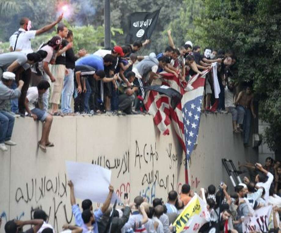 Protesters destroy an American flag pulled down from the U.S. embassy in Cairo, Egypt, Tuesday, Sept. 11, 2012. Egyptian protesters, largely ultra conservative Islamists, have climbed the walls of the U.S. embassy in Cairo, went into the courtyard and brought down the flag, replacing it with a black flag with Islamic inscription, in protest of a film deemed offensive of Islam.  (Mohammed Abu Zaid / Associated Press)