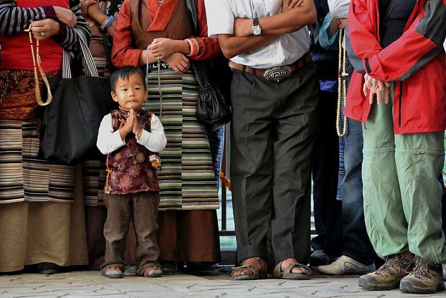 A boy praysas Tibetan Buddhist devotees wait for the arrival of spiritual leader The Dalai Lama at the  Namgyal Monastry in Dharamshala, India. Photo: Manjunath Kiran, AFP/Getty Images