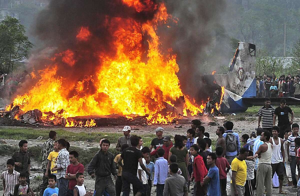 Nepalese gather around the burning wreckage at the crash site of a Sita Air airplane near Katmandu, Nepal, early Friday, Sept. 28, 2012. A plane carrying trekkers to the Everest region crashed and burned just after takeoff Friday morning in Nepal's capital, killing the 19 Nepali, British and Chinese people on board, authorities said. (AP Photo)