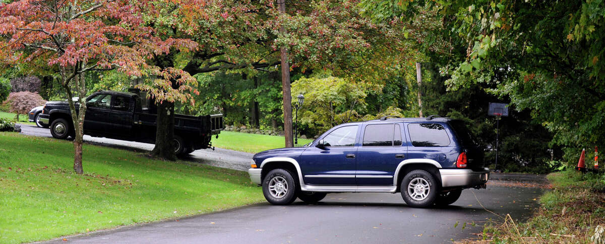 A neighbor's car blocks the end of Donnelly Drive in New Fairfield to prevent the news media from accessing the back of the Giuliano and Scocozza homes Friday, Sept. 28, 2012.