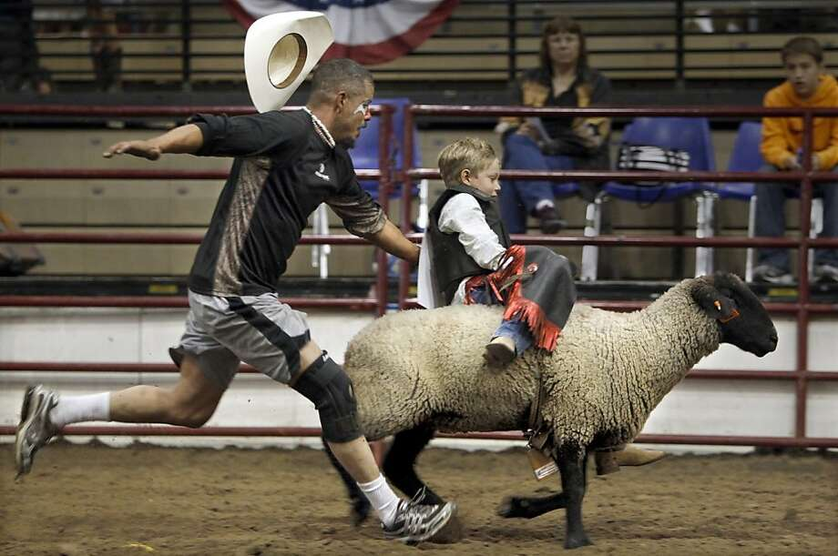 A little too wild and woolly: Josh Diggs comes to the rescue of mutton buster Wyatt Scales, who's losing his seat on a runaway sheep at the American Royal Youth Rodeo in Kansas City. Photo: Keith Myers, Associated Press