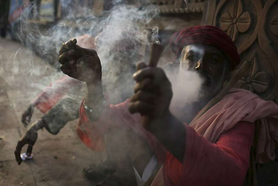 The holy high daze: A Hindu holy man, also known as a sadhu, blows clouds of marijuana smoke outside a temple in New Delhi. Photo: Kevin Frayer, Associated Press