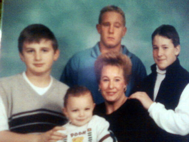 Tyler Giuliano, center, in an undated photo with his foster family. Photo: Contributed Photo