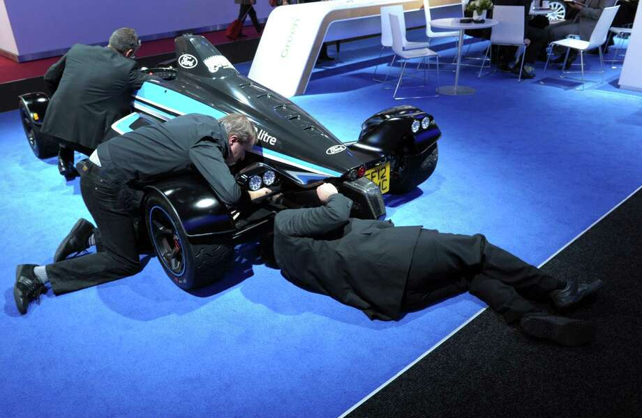 Ford staff members check a formula Ford 1.0L on the Ford stand during the press days ahead of the opening of the Paris Motor Show on Sept. 27, 2012. Photo: AFP, AFP/Getty Images / 2012 AFP