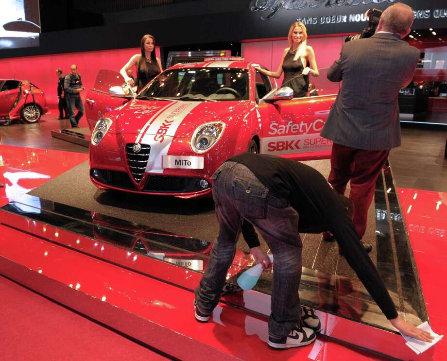 A visitor takes pictures as a staff member cleans on the Alfa Romeo stand during the press days ahead of the opening of the Paris Motor Show on Sept. 27, 2012. Photo: AFP, AFP/Getty Images / 2012 AFP