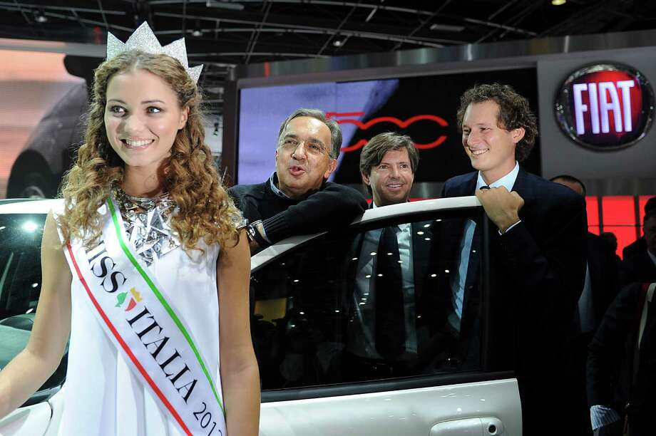 Sergio Marchionne (second from left), head of carmakers Fiat and Chrysler, Fiat brand head Olivier Francois (second from right), and Fiat chairman John Elkann (right) pose with Miss Italia, Giusy Buscemi, at the Paris Motor Show on Sept. 27, 2012. Photo: Antoine Antoniol, Getty Images / 2012 Getty Images