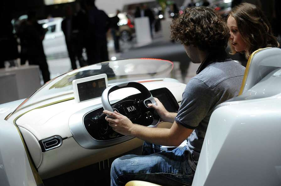 Visitors use a Kia car simulator at the Paris Motor Show on Sept. 28, 2012.