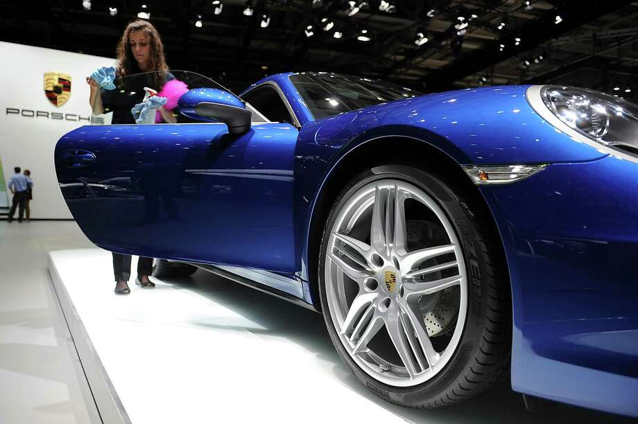 An employee cleans a Porsche Carrera 911 at the Paris Motor Show on Sept. 28, 2012. Photo: Antoine Antoniol, Getty Images / 2012 Getty Images