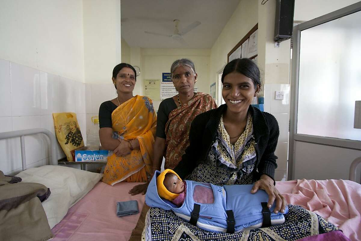 Shivamadamma, a young mother who comes from a family of rural farmers in India, gave birth to a premature baby boy weighing only 3.5 pounds. The tiny infant struggled to keep himself warm, putting his life at risk. The baby is shown at a hospital near the village of Siriminahalli, where the baby was born. He is wrapped in the Embrace infant sleeping bag. Behind him are his mother (her hand on the baby) her mother (left) and her grandmother.
