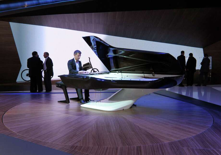 A pianist plays a piano designed by Peugeot Design Lab with Piano manufacturer Pleyel, on Sept. 27, 2012, on the stand of French carmaker Peugeot during the press days of the Paris Motor Show. Photo: AFP, AFP/Getty Images / 2012 AFP