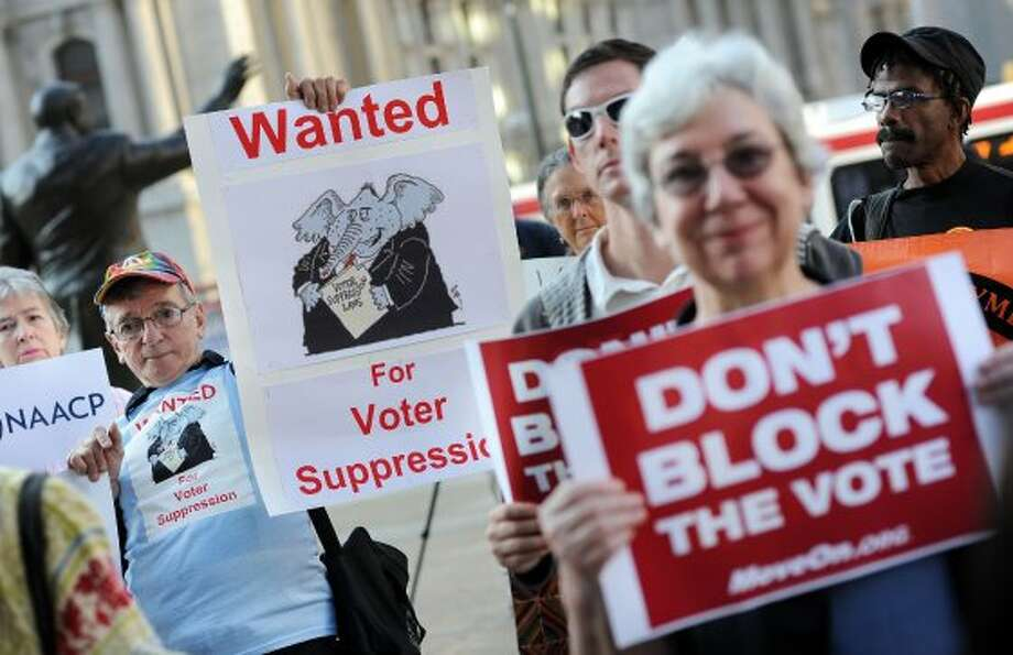 Demonstrators hold signs during a voter ID rally September 13, 2012 in Philadelphia, Pennsylvania. The Pennsylvania Supreme Court held a hearing on Pennsylvania's state Supreme Court justices on whether a law requiring photo identification from each voter should take effect for the Nov. 6 presidential election.  (William Thomas Cain / McClatchy-Tribune News Service)