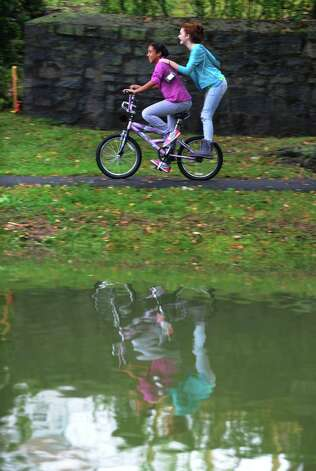 Kasey Herrer, 13, gives her friend Gillian Mariconda, 12, a ride on her bike on the path that goes along the edge of Brewsters Pond in Stratford, Conn. on Friday September 28, 2012. Photo: Christian Abraham / Connecticut Post