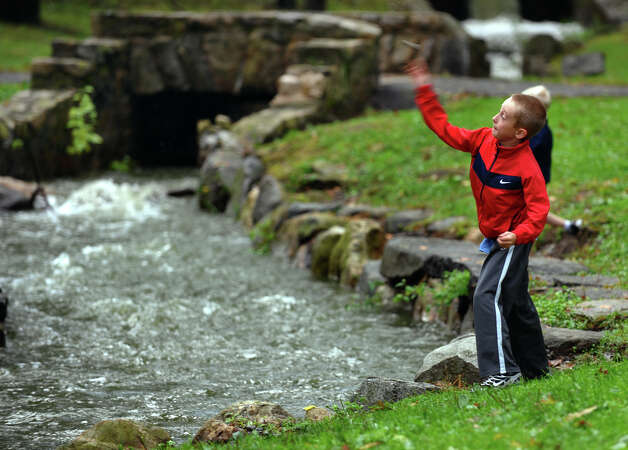 Aidan Donnelly, 9, of Middletown, tosses rocks into the swolen creek at Long Brook Park in Stratford, Conn. on Friday September 28, 2012. Photo: Christian Abraham / Connecticut Post