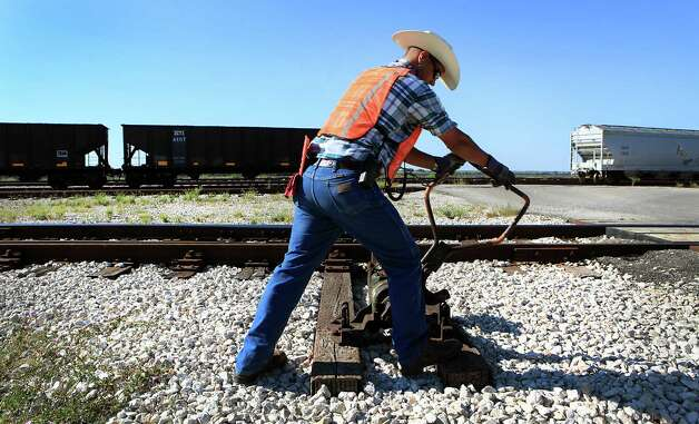 Hondo Railway railman Jarrett Persat, switches a rail line as rail cars are moved around in the yard.  The company has seen growth with the increased business from the Eagle Ford Shale oil production in south Texas.  Thursday, Sept. 20, 2012. Photo: BOB OWEN, San Antonio Express-News / © 2012 San Antonio Express-News