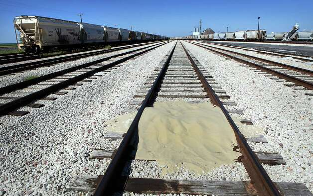 A small pile of sand used in the fracking process on the ground in the Hondo Railway yard, where other covered hopper cars wait to be unloaded and taken to fracking sites. Hondo Railway has seen growth with the increased business from the Eagle Ford Shale oil production in south Texas.  Thursday, Sept. 20, 2012. Photo: BOB OWEN, San Antonio Express-News / © 2012 San Antonio Express-News