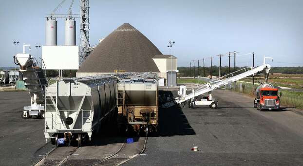 Covered hopper rail cars filled with fracking sand in the yard at Hondo Railway, as a truck is loaded with sand to be used at a south Texas fracking site.  The company has seen growth with the increased business from the Eagle Ford Shale oil production in south Texas.  Thursday, Sept. 20, 2012. Photo: BOB OWEN, San Antonio Express-News / © 2012 San Antonio Express-News