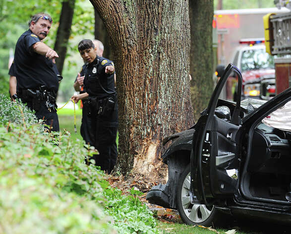 Greenwich police investigate the scene of an accident in the western lane of Round Hill Road just north of Quail Road where a car crashed into a tree, Greenwich, Friday afternoon, Sept. 28, 2012. Photo: Bob Luckey / Greenwich Time