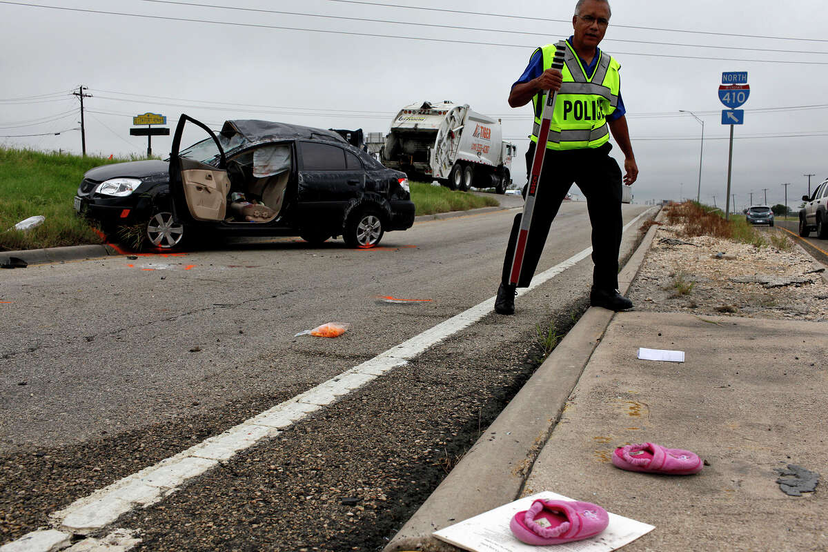 Sgt. Charlie Delgado works at the scene of a fatal car accident where a woman lost control of her car and flipped on NE Loop 410 just north of I-10 on Friday, Sept. 28, 2012. A child's slippers lay amid the items scattered from the car but the child was not in the car during the accident.