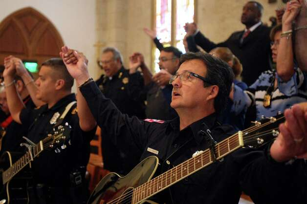 San Antonio paramedic E.J. Puente, a member of the Shields of Christ musical group, and the rest of the congregation recite the Lord's Prayer. Photo: Helen L. Montoya, San Antonio Express-News / ©SAN ANTONIO EXPRESS-NEWS