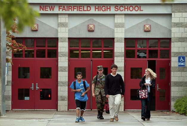 Students leave New Fairfield High School where in New Fairfield, Conn., Friday, Sept. 28, 2012.  Tyler Giuliano, a student involved in Civil Air Patrol at the school was killed by his father Jeffrey Giuliano during what appeared to be an attempted burglary early Thursday morning.  Giuliano fatally shot a masked teenager in self-defense, then discovered that he had killed his son, state police said.  (AP Photo/Jessica Hill) Photo: Jessica Hill, Associated Press / Associated Press