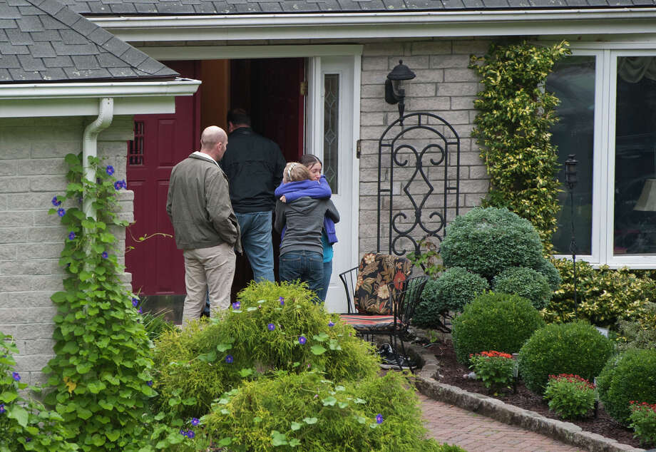 Visitors gather Friday at the home of Jeffrey Giuliano in New Fairfield, Conn., next door to where the fifth-grade teacher fatally shot an intruder during an apparent burglary - then learned that he had killed his son. Photo: Jessica Hill / FR125654 AP