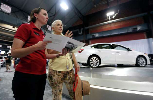Terri Raith, right, chats with Toyota product specialist Laura Voss as a 2013 Toyota Avalon sits on display in the auto pavilion during the State Fair of Texas, Friday, Sept. 28, 2012, in Dallas.  (AP Photo/LM Otero) Photo: LM Otero, Associated Press / AP