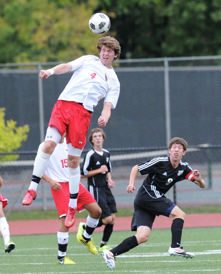 Will Gittings # 4 of Greenwich goes high for the header during the boys high school soccer match between Greenwich High School and Trumbull High School at Greenwich, Sept. 28, 2012. At right for Trumbull is Zac Chase # 8. Photo: Bob Luckey / Greenwich Time
