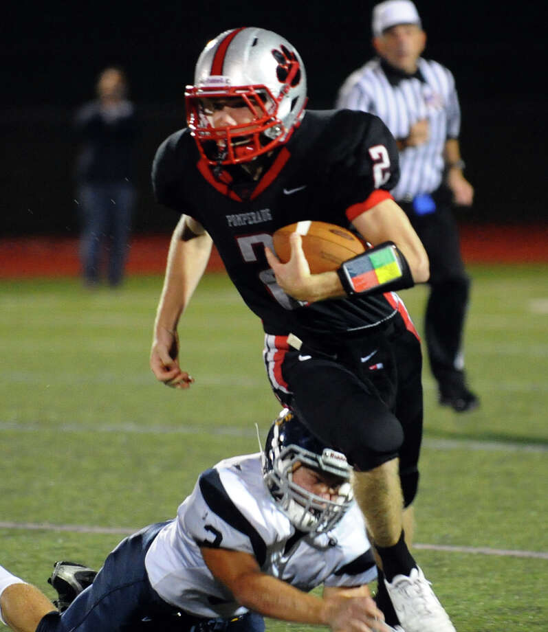 Pomperaug's #2 Eric Beatty carries the ball as Weston's #3 Aaron Pomerance tries to tackle, during football action in Southbury, Conn. on Friday September 28, 2012. Photo: Christian Abraham / Connecticut Post