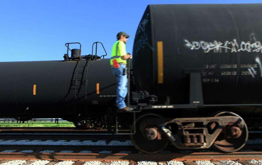 A Hondo Railway worker rides on a tanker car as it is pulled past another tanker in the yard.  The c