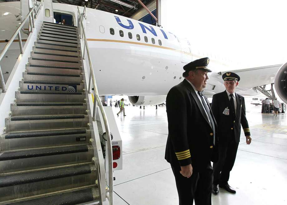Captain Dave Lundy, left, and Captain Niels Olufsen, right, stand in the hanger next to their United Boeing 787 Dreamliner after they touched down at Bush Intercontinental Airport, Friday, Sept. 28, 2012, in Houston. Photo: Karen Warren, Houston Chronicle / © 2012  Houston Chronicle