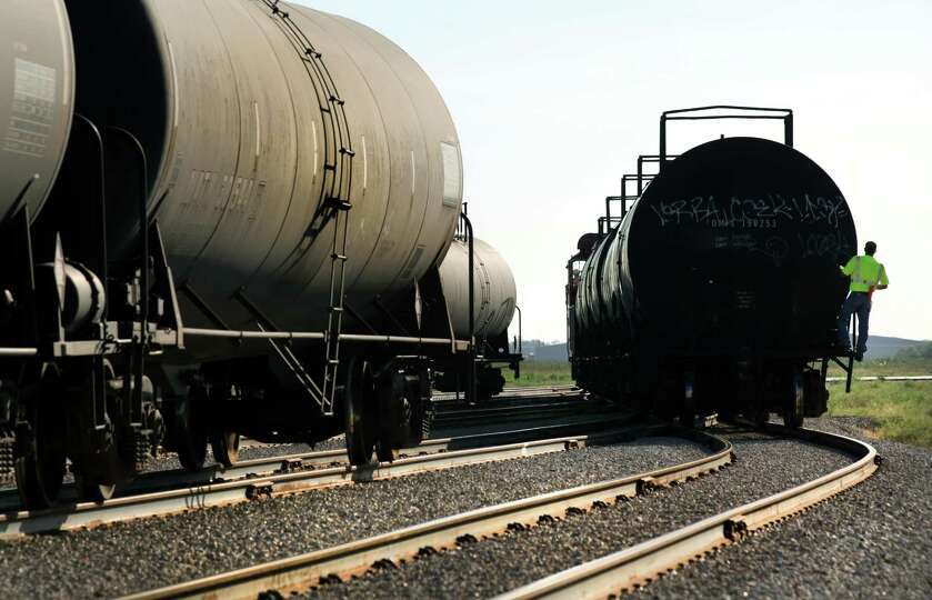 Hondo Railway worker rides on a tanker car as rail cars are moved to be unloaded.  The company has s