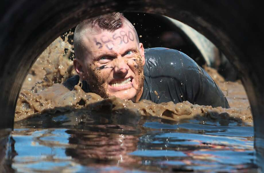 A man crawls through muddy water at the Tough Mudder. Photo: Mathew Sumner, Special To The Chronicle