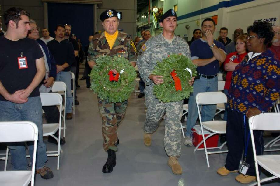 Henry Lepri and Angel Ortiz, both veterans and employees of Sikorsky Aircraft, carry wreaths to be presented during a ceremony in honor of Wreaths Across America at the Sikorsky Aircraft facility in Bridgeport, Conn. Wednesday, Dec. 9th, 2009. A Wreaths Across America convoy carrying 16,000 wreaths from Maine stopped at Sikorsky, on the way to Arlington National Cemetery in Virginia, where the wreaths will be placed on the grave of fallen soldiers. Photo: Ned Gerard / Connecticut Post