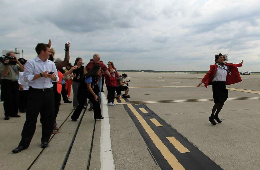 Georgina Godfrey jumps on the tarmac as she celebrates the arrival of United's first Boeing 787 Drea