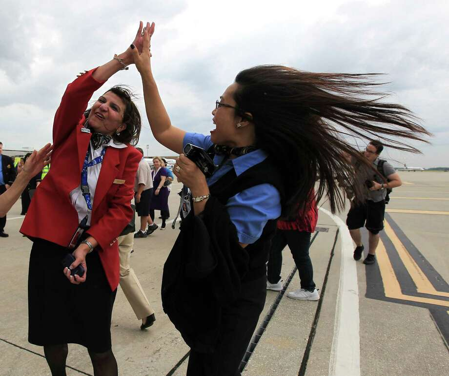 Georgina Godfrey celebrates with Gracie Rinosa, right, after the arrival of United's first Boeing 787 Dreamliner touches down at Bush Intercontinental Airport, Friday, Sept. 28, 2012, in Houston. Photo: Karen Warren, Houston Chronicle / © 2012  Houston Chronicle
